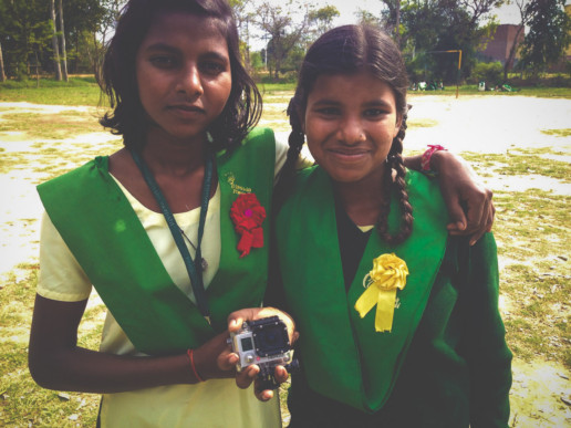 Two Young Indian girls holding goPro facing camera.
