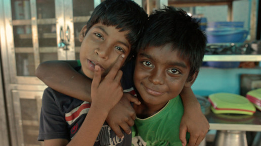 Two young Indian kids embracing while facing camera