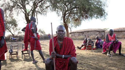 Kenyan man sitting and holding stick